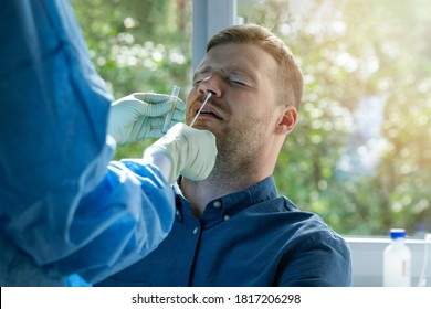coronavirus nasal swab test -  lab worker taking a mucus sample from male patient nose