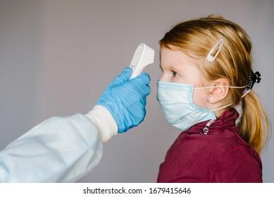 Coronavirus. Nurse oder Arzt überprüft die Körpertemperatur von Mädchen mithilfe des Infrarot-Stirn-Thermometers (Pistole) auf das Konzept des Virus - Symptom - Epidemie-Ausbruchs. Hohe Temperatur.