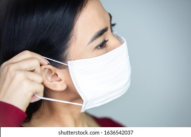 Coronavirus outbreak: An Asian woman putting on a medical disposable mask to avoid contagious viruses.