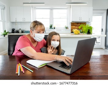 Coronavirus Outbreak. Lockdown and school closures. Mother helping bored daughter with face mask studying online classes at home. COVID-19 pandemic forces children and teachers online learning.