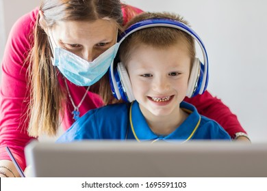 Coronavirus Outbreak. Lockdown and school closures. Mother helping his sonwith face mask studying online classes at home. COVID-19 pandemic forces children and teachers online learning.