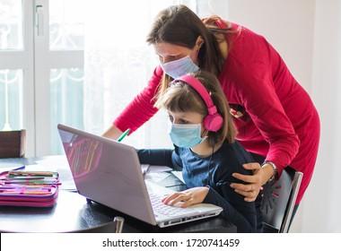 Koronavirus-Ausbruch. Schließung und Schließung von Schulen. Mutter half ihrer Tochter mit Gesichtsmaske, die zu Hause Online-Kurse studierte. COVID-19-Pandemie zwingt Kinder und Lehrer zum Online-Lernen.