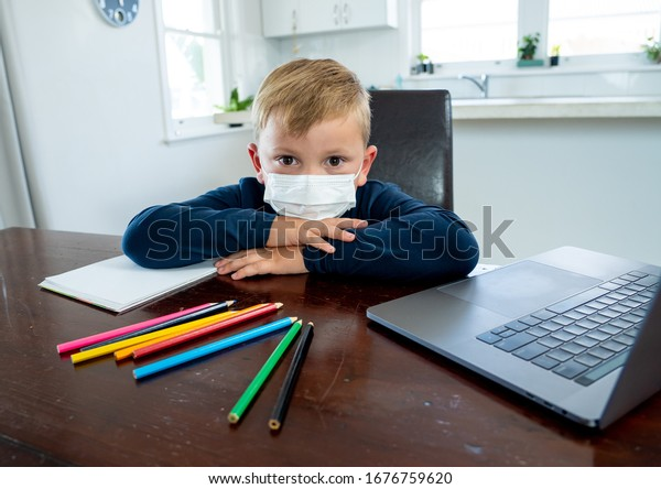 Coronavirus Outbreak. Lockdown and school closures. School boy with face mask watching online education classes feeling bored and depressed at home. COVID-19 pandemic forces children online learning.