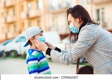Ausbruch von Coronavirus. Mutter stellt ihrem Sohn eine Gesichtsschutzmaske im Freien. Unterbindet die Ausbreitung des Coronavirus. Quarantäne. Schutzmaßnahmen. Öffentlich überfüllter Ort. Menschen verhindern eine Virusinfektion.