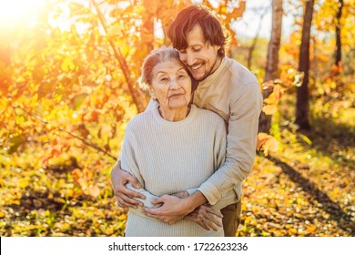 Coronavirus is over. Quarantine weakened. Take off the mask. Now you can Meet grandparents - grandmother and grandfather. Grandmother and adult grandson hugging in autumn park