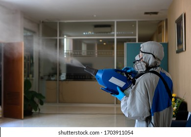 Coronavirus Pandemic. Disinfecting of office to prevent COVID-19, worker in hazmat suit with disinfect in office.