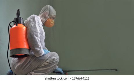 Coronavirus Pandemic. A disinfector in a protective suit and mask sprays disinfectants in the room. Prevention of Coronavirus Disease. Environmental Cleaning and Disinfection with Coronavirus Epidemic