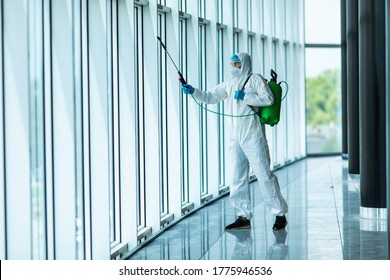 Coronavirus Pandemic. A disinfector in a protective suit and mask sprays disinfectants in office. Protection agsinst COVID-19 disease.