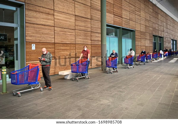 Coronavirus pandemic effects: long queue to enter the supermarket for grocery shopping. Turin, Italy - April 2020