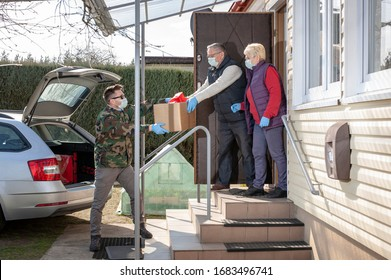 coronavirus pandemic. Epidemic. A volunteer / soldier brought food for senior citizens. On the steps, a volunteer in a medical mask and gloves passes a bag of products to an elderly couple in masks