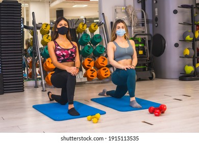 Coronavirus pandemic in gyms. Two girls stretching with face masks, social distance and the new normal