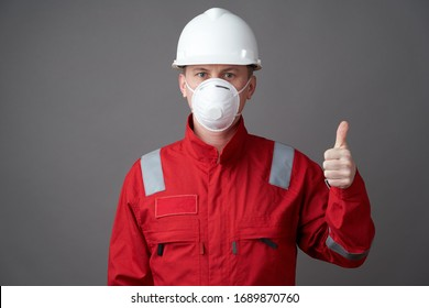 Coronavirus pandemic quarantine hygiene, Safety first. Worker man wearing hygienic mask, overall and protective hard hat. Young engineer worker wear a helmet, face mask and protective workwear suit.