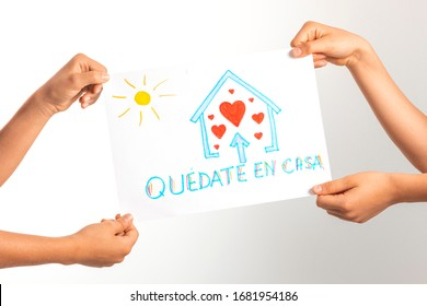 Coronavirus pandemic self quarantine at home in Spain. Kids holding drawing picture with spanish words Quedate en casa - Stay at home