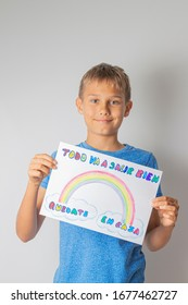 Coronavirus pandemic self quarantine in Spain. Kids at home holding pictures with spanish words Quedate en casa - Stay at home and Todo va a salir  bien - Everything will be fine