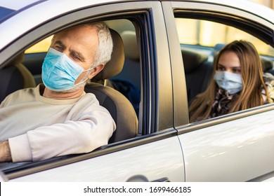 Koronavirus-Pandemie. Senior Mann, der Auto fährt, während seine Enkelin hinter dem Fenster sitzt und durch das Fenster guckt. Großvater und Enkelin in Gesichtsmaske im Auto sicher sein. Straßenverkehrssicherheit