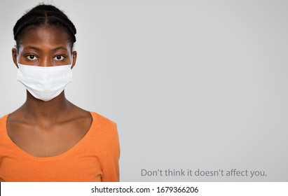 "Coronavirus Pandemic. Serious african woman in medical mask on a gray background with space for text and slogan ""Don't think it doesn't affect you""."
