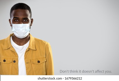 """Coronavirus Pandemic. Serious africanamerican man in medical mask on a gray background with space for text and slogan """"Don't think it doesn't affect you""""."""