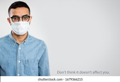 """Coronavirus Pandemic. Serious arab young man in medical mask on a gray background with space for text and slogan """"Don't think it doesn't affect you""""."""