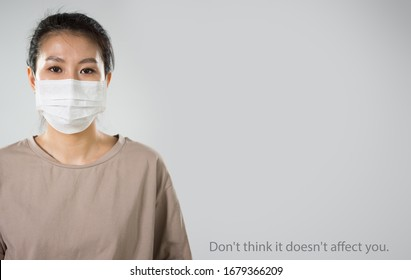 """Coronavirus Pandemic. Serious asian woman in medical mask on a gray background with space for text and slogan """"Don't think it doesn't affect you""""."""
