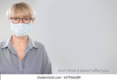 """Coronavirus Pandemic. Serious caucasian mature woman in medical mask on a gray background with space for text and slogan """"Don't think it doesn't affect you""""."""