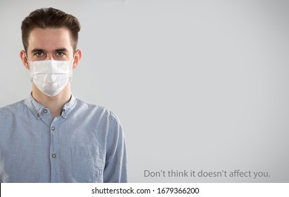 """Coronavirus Pandemic. Serious caucasian young man in medical mask on a gray background with space for text and slogan """"Don't think it doesn't affect you""""."""