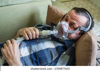 Coronavirus patient elderly man in oxygen mask in bed at home
