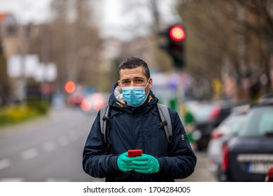 Coronavirus protection. Mature  man in the city after the work day, wearing protective mask on the face. Calling for a taxi.