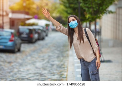 Coronavirus protection. Young woman in the city after the work day, wearing protective mask on the face. Calling for a taxi. Woman wearing mask  while waiting at the busstop after work.