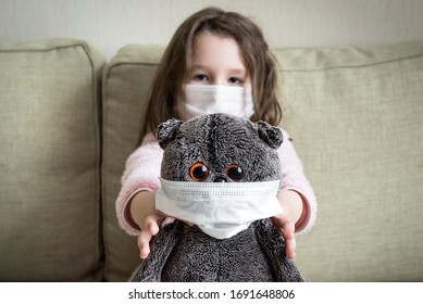 Coronavirus quarantine concept, little girl plays with toy at home during COVID-19 pandemic. Kid in medical mask for protection to corona virus indoors. Child staying in house due to coronavirus.