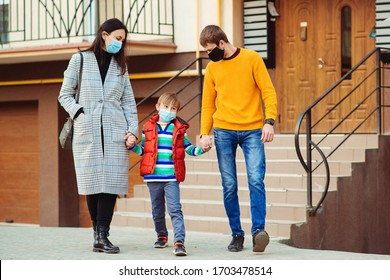 Coronavirus quarantine. Family going for a walk. Parents and kid wearing a surgical mask. Air pollution concept. Young family wearing protection face mask outdoors. Prevention coronavirus.