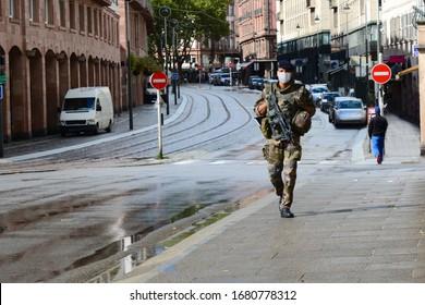 Coronavirus quarantine. French soldier in a medical mask patrols an empty city street: Strasbourg, France - September 14, 2015.
