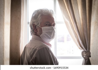 Coronavirus quarantine. Senior man wearing protective mask behind the window stay at home to avoid contagion by COVID-19 - responsibility and prevention concept
