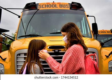 Coronavirus school: children, students, girls with face masks in front of school bus. For education, medical, health, environmental, safety concepts regarding coronavirus, back to school, facemasks.