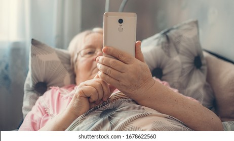 Coronavirus self-isolation advice for over-70s Elders, social isolation and loneliness in older people. Age-group risk for coronavirus. Lonely elderly woman lies in bed at home
