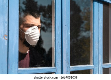 Coronavirus. Sick man of corona virus  looking through the window and wearing mask protection and recovery from the illness in home. Quarantine. Patient isolated to prevent infection. Lockdown