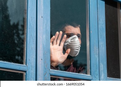 Coronavirus. Sick man of corona virus  			looking through the window and wearing mask protection and recovery from the illness in home. Quarantine. Patient isolated to prevent infection. Pandemia. House.