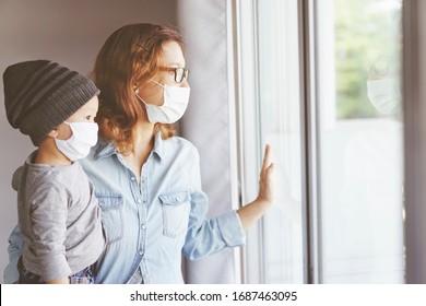 Coronavirus. Kranke Mutter und ihr Sohn schauen durch das Fenster und tragen Maske Schutz und Genesung aus dem Coronavirus oder Covid-19 zu Hause