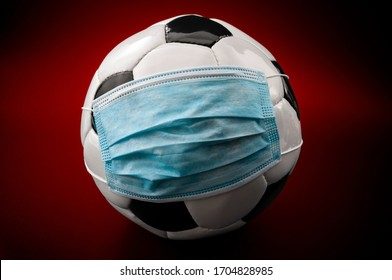Coronavirus stop soccer league and athletics competition on hold by Covid-19 epidemic concept football wearing surgical mask isolated on red ominous dark background