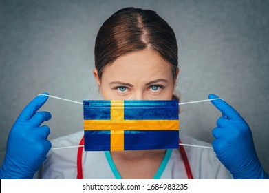 Coronavirus in Sweden Female Doctor Portrait hold protect Face surgical medical mask with Sweden National Flag. Illness, Virus Covid-19 in Sweden, concept photo