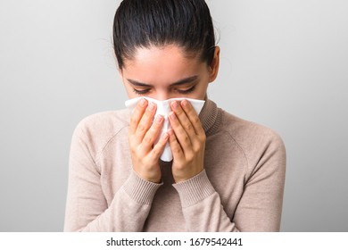 coronavirus symptoms. desperate woman with fever and headache holding a napkin or mask sneezing and coughing. keep distance and avoid crowd