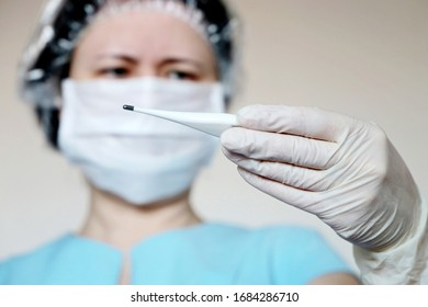 Coronavirus symptoms, woman in medical mask measures body temperature. Doctor looks at digital thermometer in her hand, concept of cold and flu
