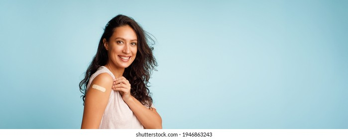 Coronavirus Vaccination Advertisement. Happy Vaccinated Woman Showing Arm With Plaster Bandage After Covid-19 Vaccine Injection Posing Over Blue Background, Smiling To Camera. Panorama, Blank Space - Shutterstock ID 1946863243