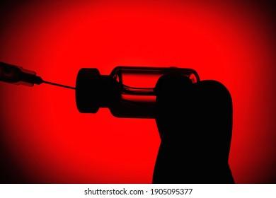 Der Coronavirus-Impfstoff und die Spritze auf rotem und schwarzem Hintergrund auf der Clearance, Silhouette. Das Konzept des Schutzes vor einer Infektion mit Coronavirus. Selektiver Fokus