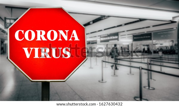 Coronavirus written on stop sign with passengers arriving at passport control within generic airport.
