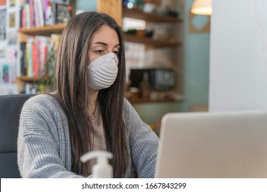 Coronavirus. Young business woman working from home wearing protective mask. Business woman in quarantine for coronavirus wearing protective mask. Working from home with sanitizer gel.