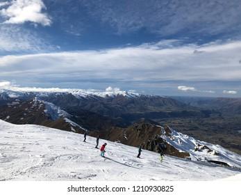 Coronet Peak, New Zealand - August 27, 2018: skiers skiing down a slope at Coronet Peak