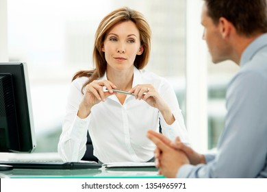 corporate business executive woman listening to young businessman in office