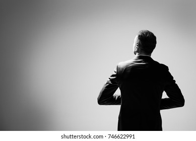 Corporate business male in modern suit standing in large empty gray space concept. man walking with confidence. Rear view. A man keeps his arms bent, his gaze is directed upwards to the right.