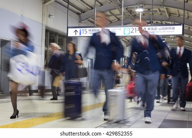 Corporate business people commuting to work by Tokyo public transport. Unrecognizable people blured in motion while rushing to train platforms.