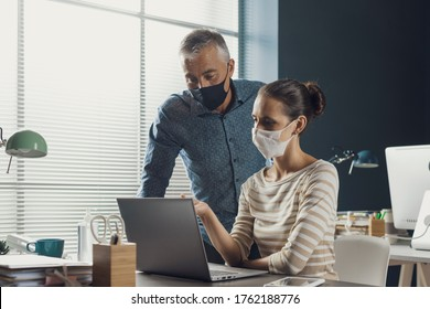 Corporate business people working together in the office, they are talking and wearing protective face masks, coronavirus covid-19 prevention mesures